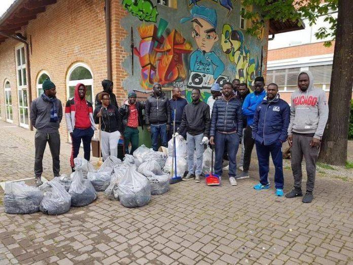 Volontari senegalesi ripuliscono l'area verde di Cascina Sacerdote