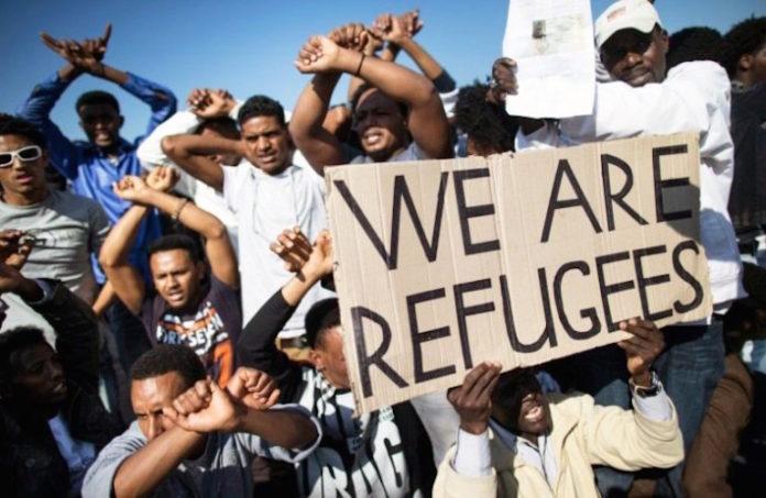 Rifugiati espongono cartello