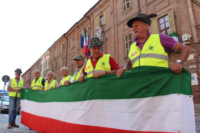 Alpini collocano bandiere italiane a Fossano in attesa del raduno