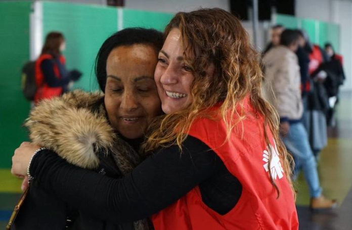 Un volontario della caritas abbraccia un migrante
