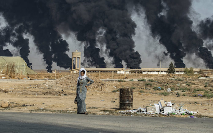 A woman stands along the side of a road on the outskirts of the town of Tal Tamr near the Syrian Kurdish town of Ras al-Ain along the border with Turkey in the northeastern Hassakeh province on October 16, 2019, with the smoke plumes of tire fires billowing in the background to decrease visibility for Turkish warplanes that are part of operation