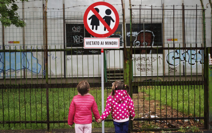 Bambini di fronte al cartello Vietato ai minori