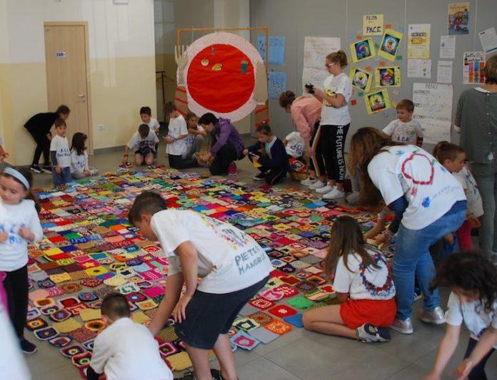San Biagio, i ragazzi dell'Acr impegnati nella composizione dei quadratini di lana per addobbare l'albero di Natale
