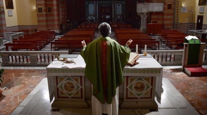 Prete celebra messa in una chiesa vuota