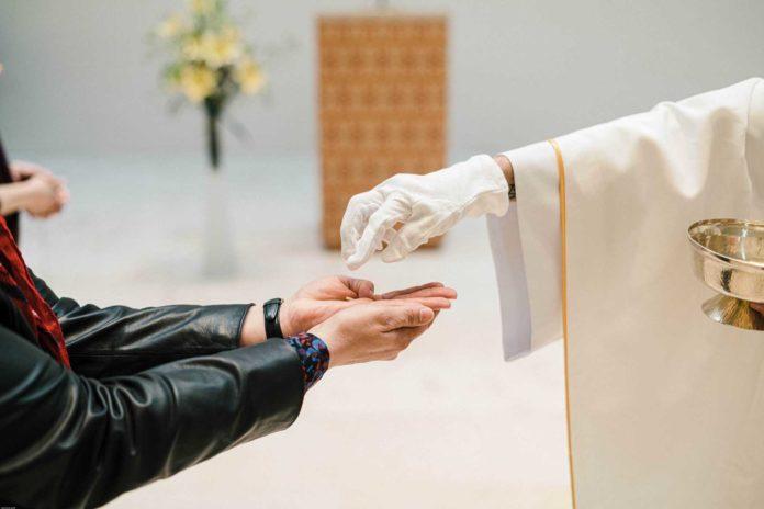 Lipsia ( Germania ), 20 aprile 2020. Chiesa della Trinità. Distribuzione della Eucarestia e distanziamento di sicurezza durante la Messa.
