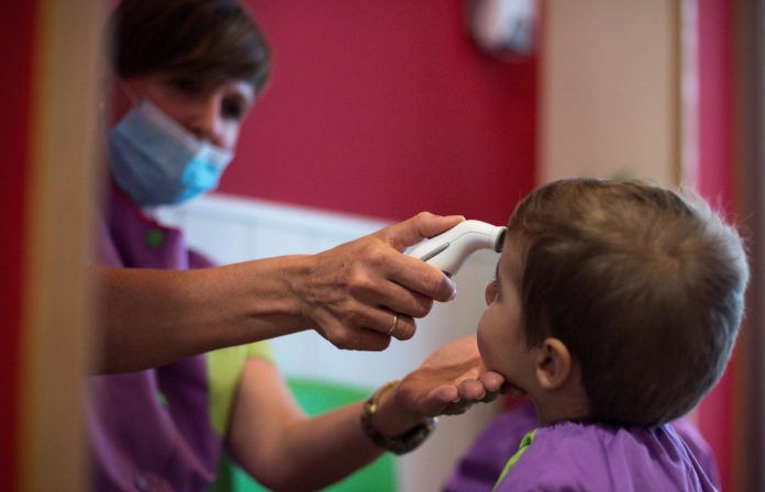 epa08639490 A teacher measures temperature to a child on the first day of classes in a school in Ourense, Galicia, 01 September 2020. Private kindergartens have been the first to start classes after the summer holidays with the protocols established to avoid coronavirus spread. EPA/Brais Lorenzo